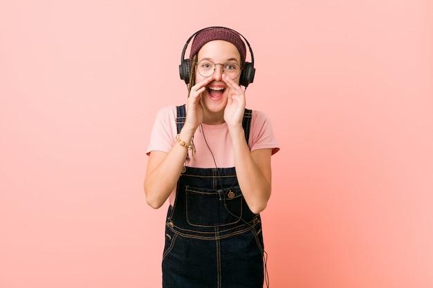 Giovane donna caucasica che ascolta la musica che grida eccitata alla parte anteriore.