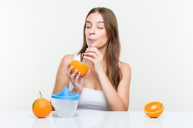 Giovane donna caucasica che beve un'arancia con una cannuccia.