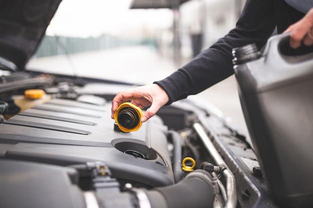 Giovane donna caucasica che controlla l'olio per motori dell'automobile. concetto di manutenzione auto.