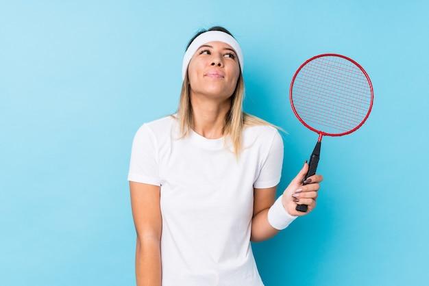 Giovane donna caucasica che gioca a badminton isolato sognando di raggiungere obiettivi e scopi