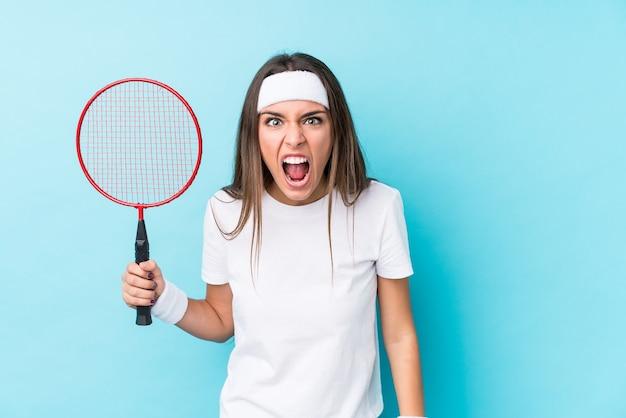 Giovane donna caucasica che gioca a badminton isolato urlando molto arrabbiato e aggressivo.