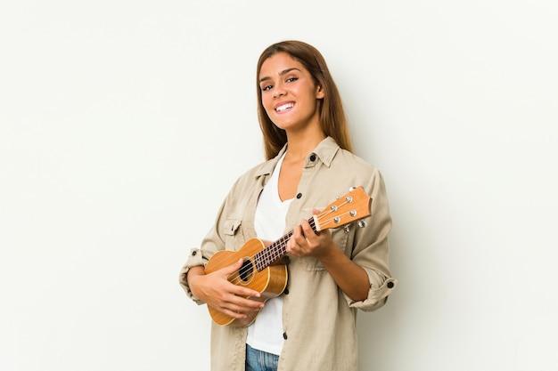 Giovane donna caucasica che gioca ukelele isolato