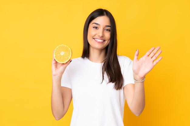 Giovane donna caucasica che giudica un'arancia isolata sulla parete gialla che saluta con la mano con l'espressione felice