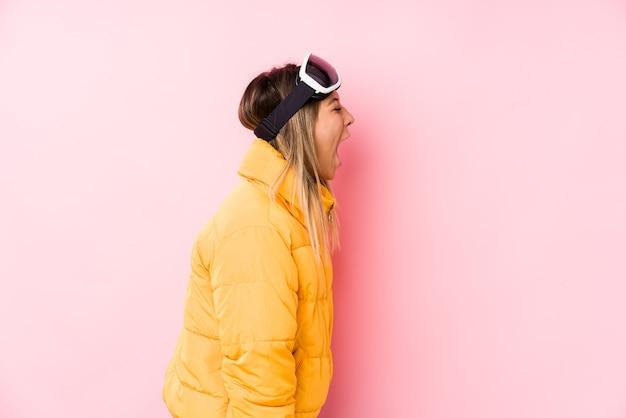 Giovane donna caucasica che indossa un abbigliamento da sci in rosa che grida verso uno spazio di copia