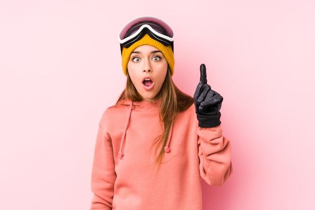 Giovane donna caucasica che indossa un abbigliamento da sci isolato avendo qualche grande idea