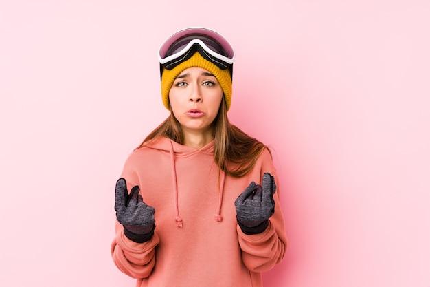 Giovane donna caucasica che indossa un abbigliamento da sci isolato che mostra che non ha soldi.