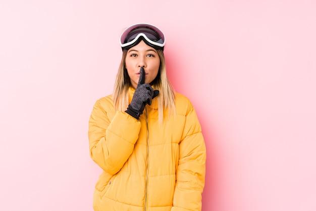 Giovane donna caucasica che indossa un abbigliamento da sci sul rosa mantenendo un segreto o chiedendo silenzio.