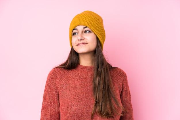 Giovane donna caucasica che indossa un berretto di lana che sogna di raggiungere obiettivi e scopi