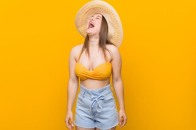 Giovane donna caucasica che indossa un cappello di paglia, look estivo rilassato e felice ridendo, collo allungato mostrando i denti.