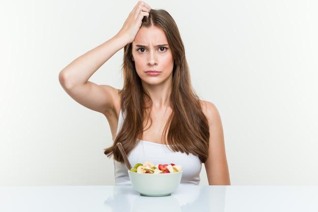 Giovane donna caucasica che mangia la ciotola di frutta che è scossa, ricorda un incontro importante.