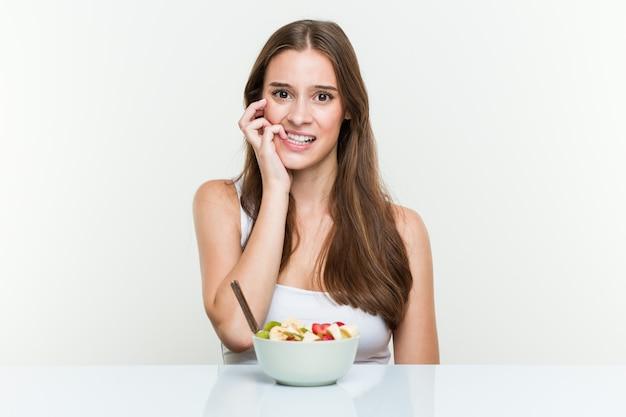 Giovane donna caucasica che mangia le unghie mordaci della ciotola di frutta, nervose e molto ansiose.
