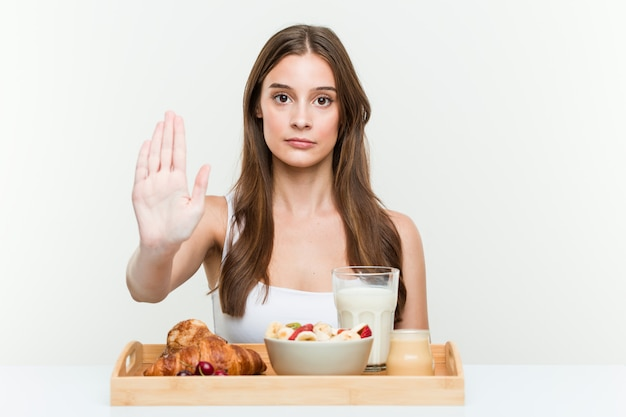 Giovane donna caucasica che mangia prima colazione che sta con il fanale di arresto di rappresentazione della mano tesa