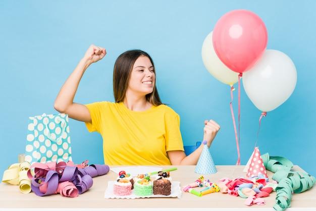 Giovane donna caucasica che organizza un compleanno che alza pugno dopo una vittoria, concetto del vincitore.