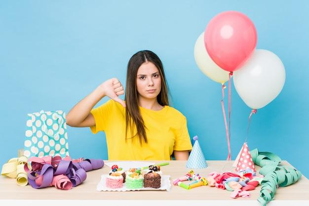 Giovane donna caucasica che organizza un compleanno che mostra un gesto di avversione, pollici giù. concetto di disaccordo.