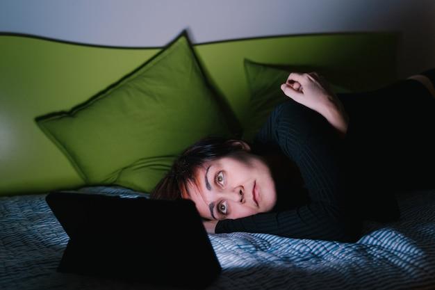 Giovane donna caucasica che prova a dormire guardando la tv a letto. le persone si sono collegate con dispositivi di intrattenimento prima di andare a letto. concetto di tecnologia e tempo libero. insonnia e insonnia.