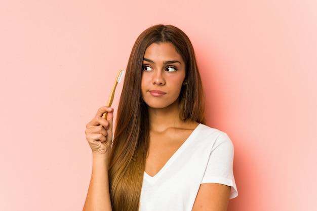 Giovane donna caucasica che pulisce i suoi denti con uno spazzolino da denti