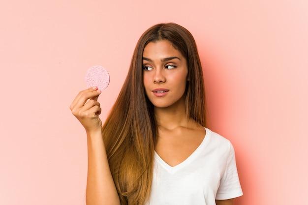 Giovane donna caucasica che pulisce il suo fronte con un disco facciale isolato