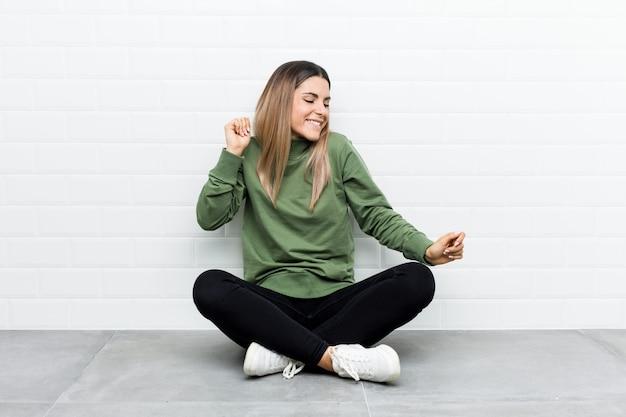 Giovane donna caucasica che si siede sul pavimento ballare e divertirsi.