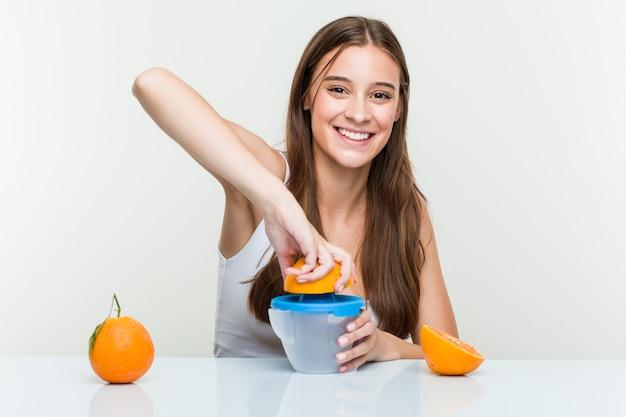 Giovane donna caucasica che tiene gli spremiagrumi arancioni