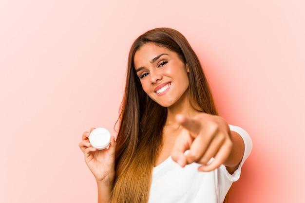 Giovane donna caucasica che tiene i sorrisi allegri di una crema idratante che indicano la parte anteriore.