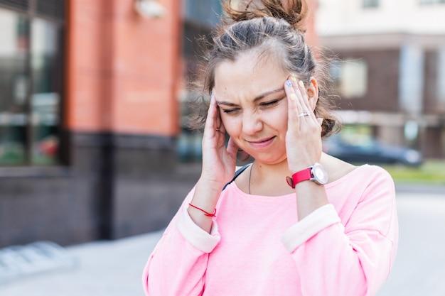 Giovane donna caucasica che tiene la sua testa che soffre di mal di testa sulla strada.