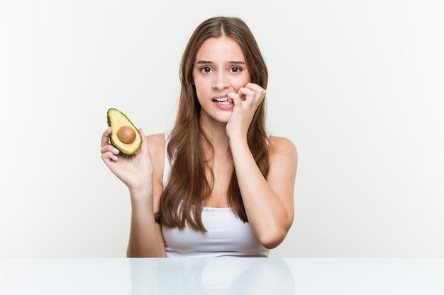 Giovane donna caucasica che tiene le unghie mordaci di un avocado, nervose e molto ansiose.