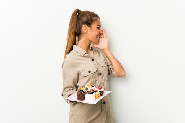 Giovane donna caucasica che tiene torte dolci gridando e tenendo il palmo vicino alla bocca aperta.