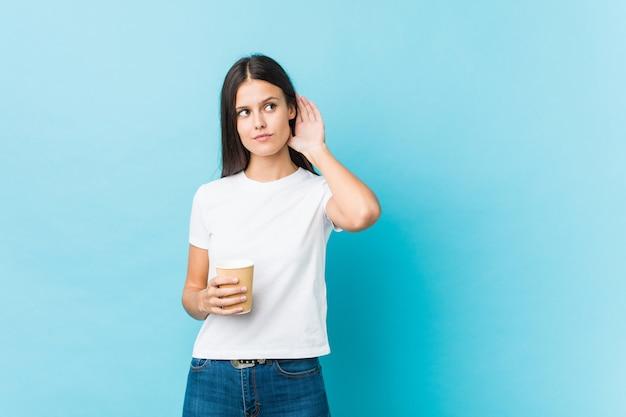Giovane donna caucasica che tiene un caffè asportabile che prova ad ascoltare un gossip.