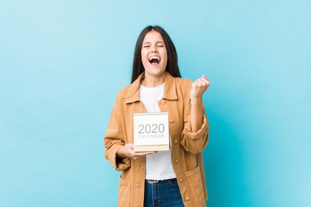 Giovane donna caucasica che tiene un calendario che incoraggia spensierato ed eccitato