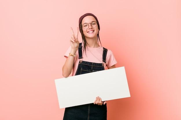 Giovane donna caucasica che tiene un cartello che mostra numero due con le dita.