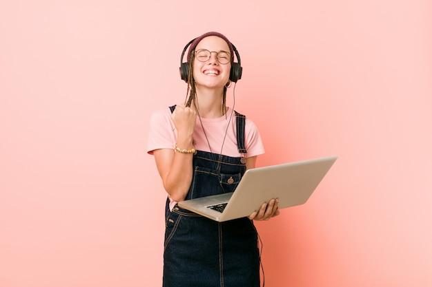 Giovane donna caucasica che tiene un computer portatile che incoraggia spensierato ed eccitato. vittoria .