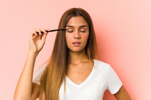 Giovane donna caucasica che tiene un eyebrush isolato