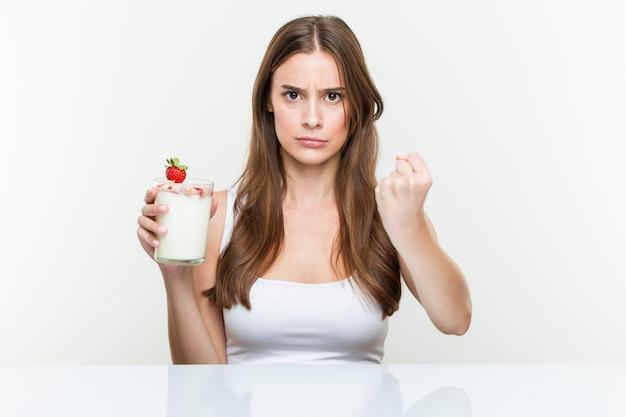 Giovane donna caucasica che tiene un frullato che mostra pugno a, espressione facciale aggressiva.