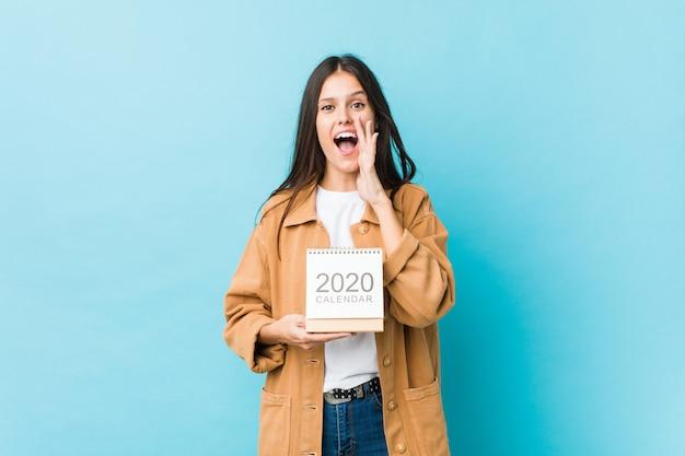 Giovane donna caucasica che tiene un gridare del calendario 2020 eccitato alla parte anteriore.