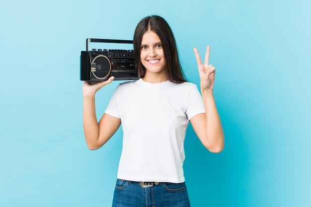 Giovane donna caucasica che tiene un guetto blaster che mostra numero due con le dita.