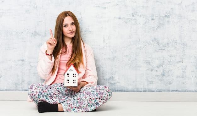 Giovane donna caucasica che tiene un'icona della casa che mostra numero uno con il dito.