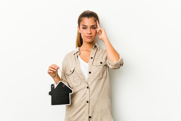 Giovane donna caucasica che tiene un'icona della casa che punta la tempia con il dito, pensando, concentrata su un compito.