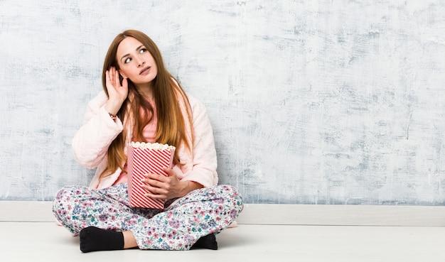 Giovane donna caucasica che tiene un secchio del popcorn che prova ad ascoltare un gossip.