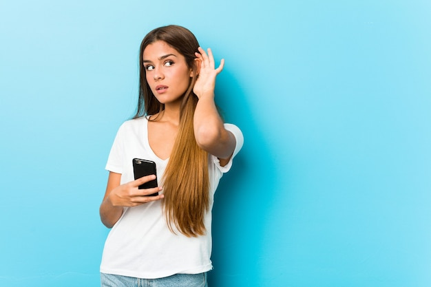 Giovane donna caucasica che tiene un telefono che prova ad ascoltare un pettegolezzo.