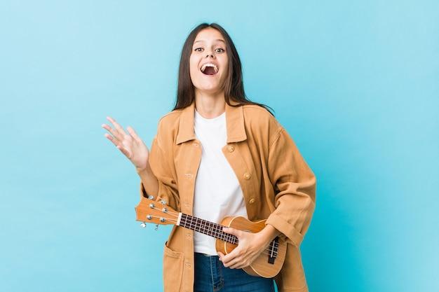 Giovane donna caucasica che tiene un ukelele che celebra una vittoria o un successo