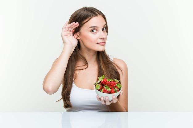 Giovane donna caucasica che tiene una ciotola di fragole che prova ad ascoltare un gossip.