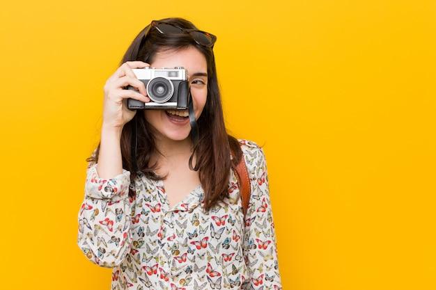 Giovane donna caucasica che tiene una macchina fotografica d'epoca