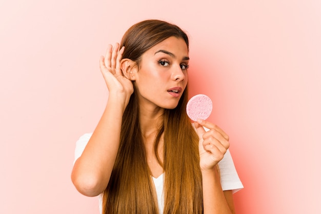 Giovane donna caucasica che tiene una spugna facciale che prova ad ascoltare un gossip.