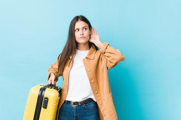 Giovane donna caucasica che tiene una valigia che prova ad ascoltare un gossip.