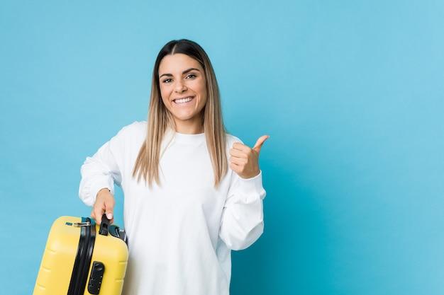 Giovane donna caucasica che tiene una valigia che sorride e che alza pollice in su