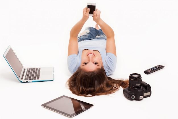 Giovane donna caucasica con dispositivi elettronici
