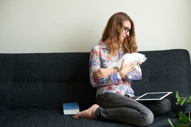 Giovane donna caucasica con gattino bianco seduto sul divano