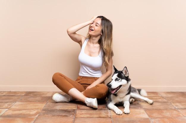 Giovane donna caucasica con il cane sopra la parete isolata