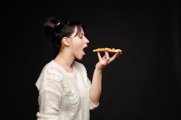 Giovane donna caucasica con la coda che mangia pezzo di pizza.