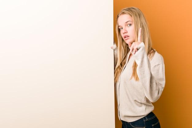 Giovane donna caucasica con lo spazio della copia che mostra numero uno con il dito.